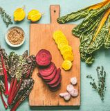 Colorful sliced beetroot on cutting board. Red and yellow beetroot with chard leaves and ingredients on kitchen table backgroun Royalty Free Stock Photo