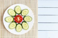 Colorful sliced fresh organic vegetables on bamboo mat. Ripe tomato and cucumber in form of flower. Top view on wooden table with. Copy space Royalty Free Stock Photos