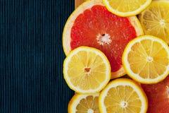 Colorful sliced fruits background. Grapefruit and lemon on blue background Stock Images