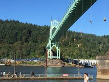 Steel Industry protesters hang from St. Johns Bridge. Colorful slings hanging from green copper bridge in Portland, Oregon USA against crowd in Cathedral Park Royalty Free Stock Photo