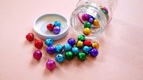 Colorful Small Bells Inside and Outside of Open Glass Bottle Stock Image