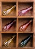 Colorful small bottles in a wooden box royalty free stock image