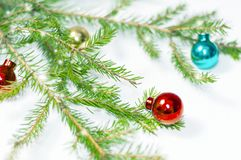 Colorful small Christmas balls on the branches of a fir tree on a white background. Christmas holiday background