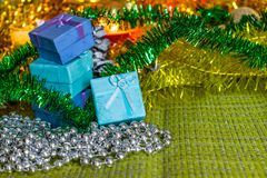 Colorful small gift boxes with gifts among Christmas tinsel and shiny toys and decorations stock images