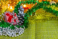 Colorful small gift boxes with gifts among Christmas tinsel and shiny toys and decorations royalty free stock photos