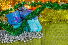 Colorful small gift boxes with gifts among Christmas tinsel and shiny toys and decorations royalty free stock images