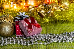 Colorful small gift boxes with gifts among Christmas tinsel and shiny toys and decorations stock image
