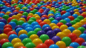 Colorful small plastic balls floating and moving in water, closeup view. Fountain or pool for children. Colorful small plastic balls floating and moving in stock footage
