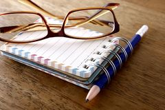 Colorful small spiral notebook, eyeglasses and a pencil on a wooden table Stock Photos
