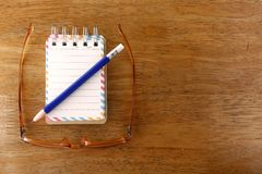 Colorful small spiral notebook, eyeglasses and a pencil on a wooden table Stock Image