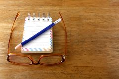Colorful small spiral notebook, eyeglasses and a pencil on a wooden table Royalty Free Stock Photography