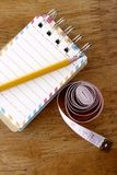 Colorful small spiral notebook, pencil and measuring tape on a wooden table Stock Photo