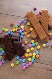 Colorful smarties among chocolate and biscuits Royalty Free Stock Photography