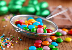 Colorful smarties in colander Stock Images