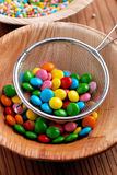 Colorful smarties in colander Royalty Free Stock Image