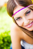 Colorful smile. Beautiful smiling brunette model wearing bright plum make-up and a purple and gold headband sitting in the park royalty free stock photo