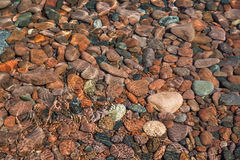 Colorful, smooth stones lie under ripples of water near the shor Stock Photography