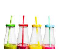 Colorful smoothies in bottles with straws, close up, isolated on white background. Stock Photos