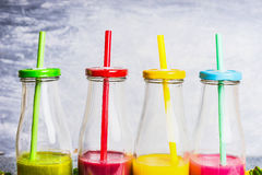 Colorful smoothies in bottles with straws, close up.  Superfoods and healthy lifestyle Royalty Free Stock Photos