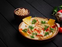 A colorful snack composition on a black wooden background. Delicious hummus spread over a dark brown wooden plate. Stock Photos