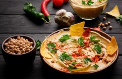 A colorful snack composition on a black wooden background. Delicious hummus spread over a dark brown wooden plate. Stock Photography