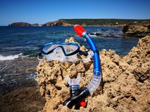 Colorful snorkel or diving mask located on the rocks. Mountain and sea background stock image