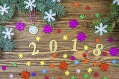 Happy New Year 2018. New Year composition with clock, snowflakes. Colorful snowflakes and spruce branches lie on the wooden background stock images