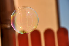 Colorful soap bubble. Floating on the blurred background  of brown fence and beige wall Stock Image