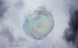 Colorful soap bubble floating in an overcast sky Stock Photography