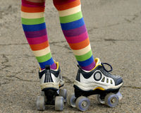 Colorful Socks and Roller Skates. A child dressed in stripes and ready to challenge a rough road royalty free stock photo