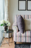 Colorful sofa with pillows and glass table in living room Stock Photography