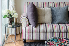 Colorful sofa with pillows and glass table in living room Royalty Free Stock Images