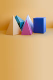 Colorful solid figures still life background. Three-dimensional prism pyramid rectangular cube objects on orange. Yellow. Blue pink green colored geometric stock photos