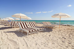 Colorful South Beach Umbrellas and Lounge Chairs. Colorful beach umbrellas and lounge chairs along the shoreline in trendy and popular South Beach in Miami stock photo