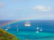 A colorful spectrum over admiralty bay. A rainbow arching over the sailing ship sea cloud in the grenadines royalty free stock images