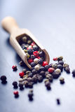Colorful spices on a dark blue table. Concept of kitchen and cooking. Spicy on a wooden spoon. Stock Photos