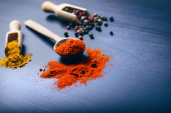 Colorful spices on a dark blue table. Concept of kitchen and cooking. Spicy on a wooden spoon. Royalty Free Stock Images