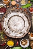 Colorful spices and herbs around empty vintage plate on rustic wooden background, top view Royalty Free Stock Photography