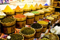 Traditional spices market - pots and wooden tubs stand in row with tea, spices, fruits, roots, flowers. Street bazaar. Colorful spices powders and herbs in Stock Images