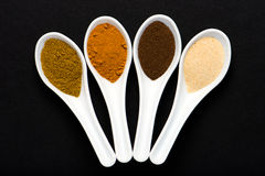 Colorful spices in spoons over black Stock Images