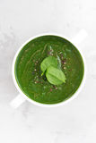 Colorful spinach cream soup on a white background, top view Stock Photos