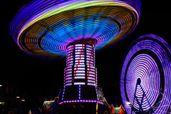 Colorful Spinning Swings, Ferris Wheel at Night Royalty Free Stock Photography
