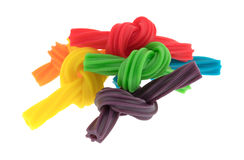 Colorful spiral licorice sticks tied in knots. A group of colorful spiral licorice sticks that have been tied in small knots isolated on a white background stock photo