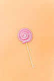 Colorful spiral lollipop on orange background Stock Photography