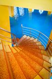 Colorful spiral stairway with blue floor stock photography