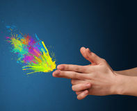 Colorful splashes are coming out of gun shaped hands Stock Images
