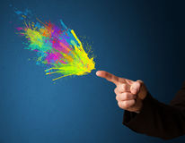 Colorful splashes are coming out of gun shaped hands Royalty Free Stock Photo