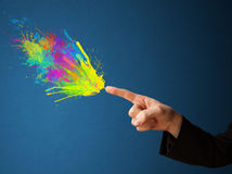 Colorful splashes are coming out of gun shaped hands Royalty Free Stock Photography
