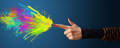 Colorful splashes are coming out of gun shaped hands Stock Image