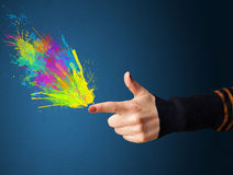 Colorful splashes are coming out of gun shaped hands Stock Photography